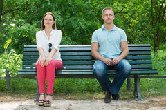 Shy Man And Woman Sitting On Bench stock image