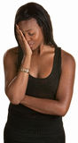 Shy Young Woman. Shy young black woman with face in hand Royalty Free Stock Images