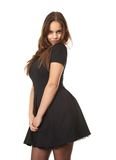 Shy young woman in black dress. Portrait of a shy young woman in black dress standing on isolated white background Royalty Free Stock Photography