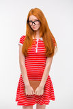 Shy young woman with long red hair holding a book Royalty Free Stock Image