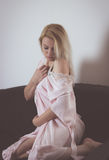 Shyness. Blond woman holding and pulling back pink robe Royalty Free Stock Photography