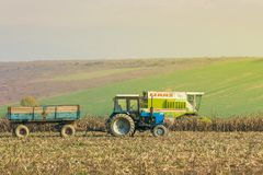 Tractor and harvester in autumn field. Shyroke, Ukraine - NOV 11, 2015: tractor and harvester in the field among the corn stalks in late fall haze day Stock Image