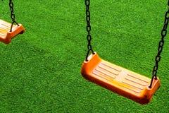 Siège d'oscillation sur le terrain de jeu artificiel d'herbe photographie stock