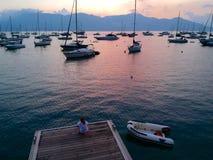 Siège de femme sur un dock regardant le beau coucher du soleil de mer avec le voilier sur la mer et la montagne sur le fond images stock