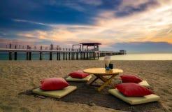 Siège dinant crépusculaire exotique sur la plage images libres de droits