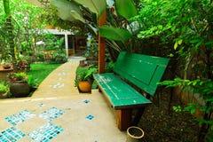 Siège en bois sur la plate-forme parmi le jardin floral images stock