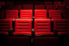 Siège rouge dans la salle de cinéma Fond trouble Photographie stock