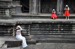 Sièges asiatiques de fille sur les ruines d'Angkor Vat Image libre de droits