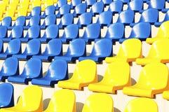 Sièges bleus et jaunes vides dans le stade Images stock
