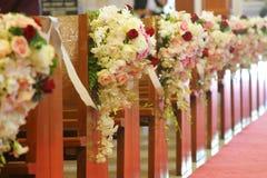 Sièges d'église décorés des bouquets Photographie stock