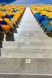 Sièges de stade et escaliers jaunes et bleus de stade Images stock