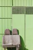 Sièges de voiture jetés devant une porte verte de garage Photo stock