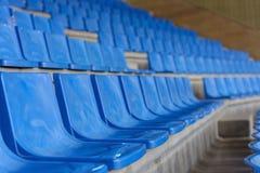 Sièges en plastique bleus dans une salle de gymnastique dans une rangée Image libre de droits