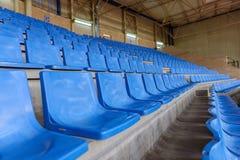 Sièges en plastique bleus dans une salle de gymnastique dans une rangée Photographie stock libre de droits