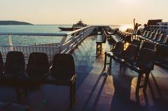 Sièges sur un ferry au coucher du soleil Photo stock