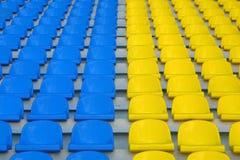 Sièges vides bleus et jaunes de stade Photo stock