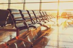 Sièges vides dans le salon de départ à l'aéroport au coucher du soleil Photo libre de droits