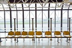 Sièges vides dans le salon de départ à un aéroport Images libres de droits