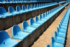 Sièges vides en plastique bleus sur le stade Photos stock