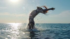 Siła mężczyzny kąpanie w morzu bawić się długie włosy otaczającego bryzgać przy zmierzchu zwolnionym tempem zbiory