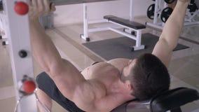 Siła trening, mięśniowy bodybuilder robi ławki prasie z barbell podczas gdy sporty zasilają szkolenie w sprawności fizycznej stud zdjęcie wideo