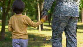 Siły zbrojne żołnierza mienia syna ręka wpólnie i odprowadzenie w parku, rodzinna miłość zdjęcie wideo