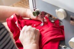 Si för äldre kvinna som fixar röd jeans på en symaskin Royaltyfri Fotografi