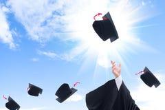 Si laurea i cappelli di lancio di graduazione nell'aria Immagine Stock