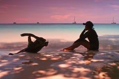 Si siede sulla spiaggia Fotografia Stock