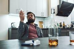 Si usted está crónico abajo, es una lucha de por vida a guardar del hundimiento Hombre borracho que se sienta en la tabla con alc fotos de archivo