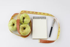 Sia a dieta il concetto con la mela verde, un taccuino, la penna e una t di misurazione Fotografie Stock