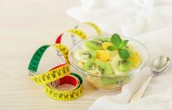 Sia a dieta il concetto del kiwi, l'arancia, ciotola di macedonia della banana sui precedenti bianchi Immagine Stock