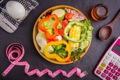 Sia a dieta il piano, la misura di nastro, il calcolatore per le calorie di conteggio, insalata fotografia stock