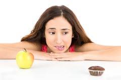Sia a dieta la donna che guarda ad un muffin e ad una mela Fotografia Stock Libera da Diritti
