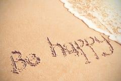 Sia felice scritto sulla sabbia Immagini Stock Libere da Diritti