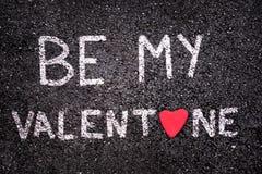 Sia il mio biglietto di S. Valentino scritto su asfalto con una pietra rossa sotto forma di un cuore Fotografie Stock Libere da Diritti