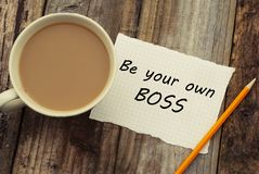 Sia la vostra propria iscrizione motivazionale del capo su Libro Bianco, con la tazza di caffè sopra la tavola di legno di rustci fotografia stock