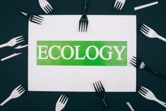 Sia liberamente di plastica Carta con ecologia di parola nel centro delle forcelle di plastica in bianco e nero monouso su fondo  fotografie stock libere da diritti