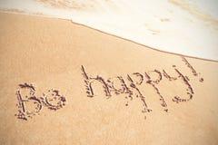 Sia testo felice scritto sulla sabbia Immagine Stock