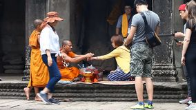 Siam Reap Angkor Wat, Cambodia - January 12, 2017:Cambodian buddhist monk reading mantra for tourist.Tourists and stock video