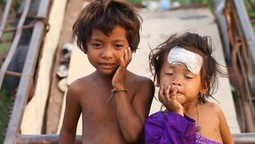 Siam Reap, Cambodia - January 14, 2017: A homeless boy with his young sister living in a house from empty boxes and
