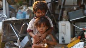 Siam Reap Cambodja - Januari 14, 2017: En hemlös pojke med hans unga systeruppehälle i ett hus från tomma askar och