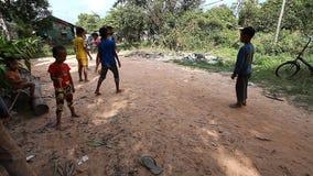 Siam Reap, Camboja - 13 de janeiro de 2017: Futebol cambojano do jogo de crianças na estrada em sua vila pobre Vida dentro filme