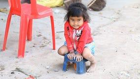 Siam Reap, Kambodja - Januari 14, 2017: Een kleine Cambodjaanse meisjesspelen naast huisvuil en afval Het leven in de krottenwijk stock footage