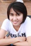 Siamesische Frau, die auf einer Bank sitzt Stockfoto