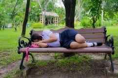 Siamesisches Schulmädchen, das auf der Bank schläft Lizenzfreie Stockfotografie