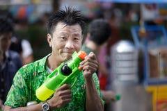 Siamesisches songkran Festival: Mannholding sprizen Gewehr Lizenzfreie Stockfotografie