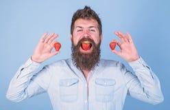Siamo che cosa mangiamo L'uomo gode del gusto della bacca Pantaloni a vita bassa barbuti della bocca della bacca Concetto dolce d immagini stock