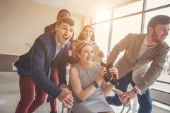Siamo i vincitori gente di affari divertendosi mentre correndo sulle sedie dell'ufficio immagini stock