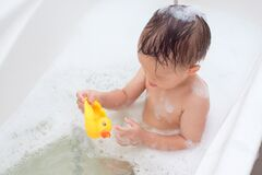 Free Sian 2 Years Old Toddler Baby Boy Child Having Fun Sitting In Bathtub Playing Rubber Duck Toy And Take A Shower By Himself In The Stock Images - 185709794